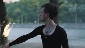 Портрет молодого профессионального человека выполняя шоу с положением вентилятора огня на берег реки береге реки перед деревьями  сток-видео