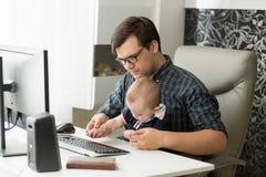 Портрет молодого работающий на самого себя человека работая дома офис на компьютере и смотря после его сына младенца Стоковые Изображения RF