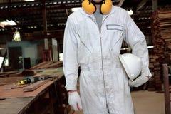 Портрет молодого работника в белом равномерном держа шлеме безопасности в мастерской плотничества Стоковое Изображение