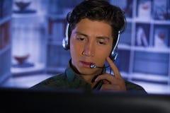 Портрет молодого солдата нося военную форму, воинский оператора трутня наблюдая на его компьютере и говорить Стоковые Фото