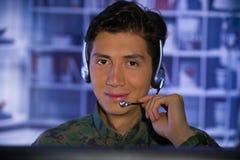 Портрет молодого солдата нося военную форму, воинский оператора трутня наблюдая на его компьютере и говорить Стоковое фото RF