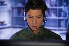 Портрет молодого солдата нося военную форму, воинский оператора трутня наблюдая на его компьютере и говорить Стоковая Фотография RF