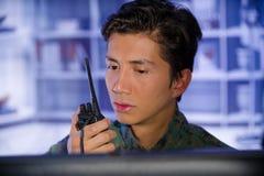Портрет молодого солдата нося военную форму, воинский оператора трутня наблюдая на его компьютере и используя радио Стоковая Фотография