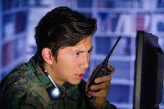 Портрет молодого солдата нося военную форму, воинский оператора трутня наблюдая на его компьютере и используя радио Стоковые Фото