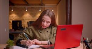 Портрет молодого сочинительства девочка-подростка в тетради будучи сконцентрированным в офисе видеоматериал