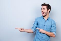 Портрет молодого стильного парня в рубашке джинсов, указывая на copysp стоковые фотографии rf