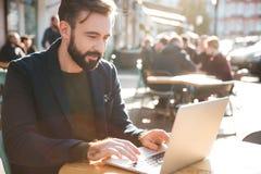 Портрет молодого стильного человека работая на портативном компьютере стоковое фото