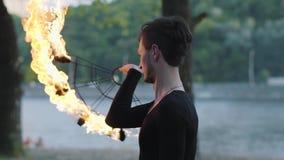 Портрет молодого тонкого человека выполняя шоу с положением вентилятора огня на берег реки береге реки перед деревьями Умелое fir видеоматериал