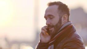 Портрет молодого усмехаясь бизнесмена говоря используя смартфон на заходе солнца в современном большом городе видеоматериал