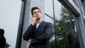 Портрет молодого успешного задумчивого бизнесмена в городе Человек в куртке дела на предпосылке офисного здания красиво акции видеоматериалы