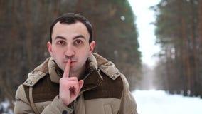 Портрет молодого человека в куртке делает для того чтобы заставить замолчать жест Человек стоит в лесе зимы сток-видео