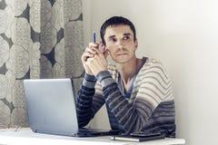 Портрет молодого человека в случайной носке на деятельности работы на ноутбуке смотря с внимательную сторону стоковая фотография rf