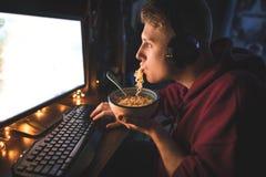 Портрет молодого человека есть суп лапши и наслаждаясь компьютером вечером дома стоковое фото