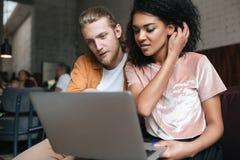 Портрет молодого человека и девушки сидя в ресторане и работая на компьтер-книжке Славная Афро-американская девушка с темное курч Стоковое Изображение RF