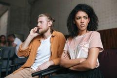 Портрет молодого человека и девушки сидя на кафе Расстроенная Афро-американская девушка при темное вьющиеся волосы заботливо смот Стоковое Изображение
