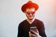 Портрет молодого человека смотря сотрясенный на смартфоне над белой предпосылкой студии стоковые фото