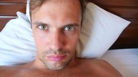 Портрет молодого человека с придурковатой гримасой, лежа на кровати замедленное движение 4k акции видеоматериалы