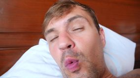 Портрет молодого человека с придурковатой гримасой, лежа на кровати замедленное движение 4k сток-видео