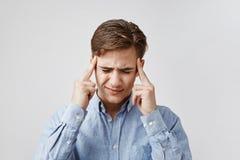 Портрет молодого человека с ужасной головной болью Гай чувствует как боль идет через его мозг Отвлечена персона и Стоковое Изображение RF