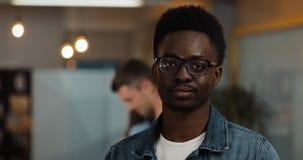 Портрет молодого черного усмехаясь успешного бизнесмена нося стильные стекла стоя в современном офисе Трудовой народ стоковая фотография rf