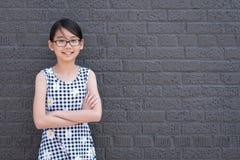 Портрет молодой азиатской девушки против черной кирпичной стены стоковые изображения rf