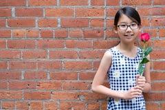 Портрет молодой азиатской девушки с цветком красной розы против красной кирпичной стены стоковое изображение