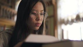 Портрет молодой азиатской книги чтения женщины сидя на таблице в библиотеке видеоматериал