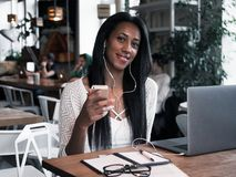 портрет молодой африканской женщины ослабляющ в кафе с компьтер-книжкой Стоковые Фото