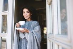 Портрет молодой Афро-американской девушки обернутой в кофе шотландки выпивая в даме ресторана славной усмехаясь с темное курчавым Стоковое фото RF