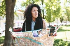 Портрет молодой Афро-американской девушки уныло смотря в сторону с картой в руках на маленькой девочке улицы с темным вьющиеся во стоковое фото