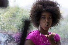 Портрет молодой афро американской женщины в спортзале пока слушая mus Стоковое Изображение RF