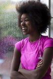 Портрет молодой афро американской женщины в спортзале пока слушая mus Стоковая Фотография