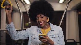 Портрет молодой Афро-американской женщины нося I с наушниками слушая музыку, поет и смешные танцы публично акции видеоматериалы