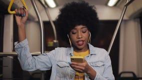 Портрет молодой Афро-американской женщины нося I с наушниками слушая музыку, поет и смешные танцы публично сток-видео