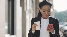 Портрет молодой Афро-американской коммерсантки в костюме, идущ вокруг города, выпивая кофе и использования видеоматериал