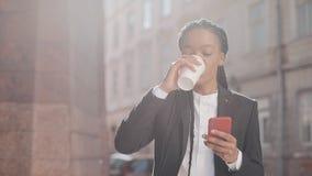 Портрет молодой Афро-американской коммерсантки в костюме, идя вокруг города около бизнес-центра, выпивая видеоматериал