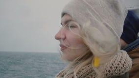 Портрет молодой белокурой женщины путешествуя на шлюпке в погоде overcast Женщина при человек смотря на море и волнах сток-видео
