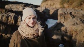 Портрет молодой белокурой женщины стоя в горах и усмехаясь к приходя человеку, волосам развевая на ветре акции видеоматериалы