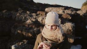 Портрет молодой белокурой женщины стоя в горах в солнечном дне и принимая фото selfie на smartphone видеоматериал
