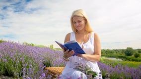 Портрет молодой белокурой книги чтения женщины в поле лаванды на утре Стоковая Фотография