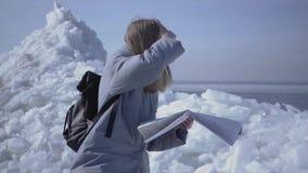 Портрет молодой белокурой милой женщины в теплом положении куртки на леднике проверяя с картой Изумляя природа  сток-видео