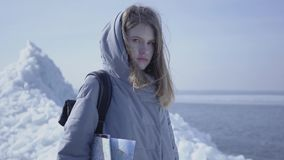 Портрет молодой белокурой милой женщины в теплом положении куртки на леднике с картой в руках, смотря в камере сток-видео