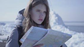 Портрет молодой белокурой милой женщины в теплом положении куртки на леднике с картой в руках, смотря вокруг _ сток-видео