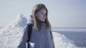 Портрет молодой белокурой милой женщины в теплом положении куртки на леднике с картой в руках, смотря вокруг _ видеоматериал