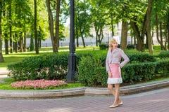Портрет молодой блондинкы в розовом костюме в парке outdoors Стоковые Фото