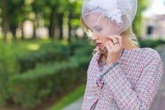 Портрет молодой блондинкы в розовом костюме в парке outdoors Стоковые Фотографии RF