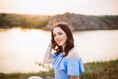 Портрет молодой женщины в голубом романтичном платье со шляпой сидя около реки и наслаждаясь вечером захода солнца Спокойствие и  стоковые фото