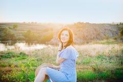 Портрет молодой женщины в голубых романтичных платье и соломенной шляпе в свете солнца наслаждаясь заходом солнца лета на природе стоковое фото