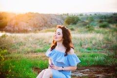 Портрет молодой женщины в голубых романтичных платье и соломенной шляпе в свете солнца наслаждаясь заходом солнца лета на природе стоковые изображения