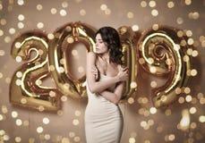 Портрет молодой женщины в обнаженном платье s под boke имея потеху с воздушным шаром золота 2019 стоковая фотография rf